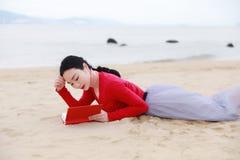 Den unga asiatiska kinesiska kvinnan läste att ligga på hennes sida i sandläseboken på stranden royaltyfria bilder