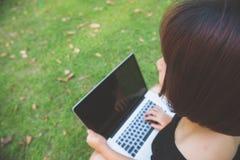 Den unga asiatiska kvinnan lägger benen på ryggen på det gröna gräset med den öppna bärbara datorn Flickahänder på tangentbordet  Arkivbild