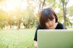 Den unga asiatiska kvinnan lägger benen på ryggen på det gröna gräset med den öppna bärbara datorn Flickahänder på tangentbordet  Royaltyfri Foto
