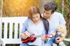 Den unga asiatiska kvinnan och mannen kopplar ihop sammanträde på parkerar att spela ukulelet Fotografering för Bildbyråer