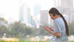 Den unga asiatiska kvinnan ska tycka om liftstyle, genom att lyssna till musik med den trådlösa headphonen arkivfilmer