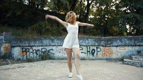 Den unga asiatiska kvinnan som dansar modern koreografi i stad, parkerar, utanför Staden fördärvar och grafittivariation lager videofilmer