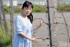 Den unga asiatiska kvinnan står på ett taggtrådstaket Royaltyfri Foto