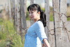 Den unga asiatiska kvinnan står på ett taggtrådstaket Royaltyfri Bild