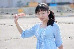 Den unga asiatiska kvinnan står på ett taggtrådstaket Arkivbild