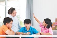 Den unga asiatiska läraren frågar frågan unga ungar i klassrum Royaltyfria Foton