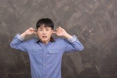 Den unga asiatiska mannen äcklade den unga mannen som pluggar hans öron för att vägra Royaltyfri Fotografi