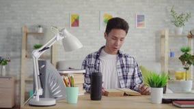 Den unga asiatiska mannen i en skjorta läser en bok och använder en stämmaassistent lager videofilmer