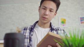 Den unga asiatiska mannen i en skjorta läser en bok och använder upp ett stämmaassistentslut stock video