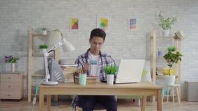 Den unga asiatiska mannen i en skjorta skriver in data med en kontokort på en bärbar dator lager videofilmer