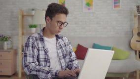 Den unga asiatiska mannen i stilfulla exponeringsglas inaktiverade i en rullstol med en bärbar dator i vardagsrummet av huset stock video