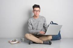 Den unga asiatiska mannen i tillfällig kläder använder en bärbar dator som ler whi Royaltyfria Foton