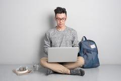 Den unga asiatiska mannen i tillfällig kläder använder en bärbar dator som ler whi Arkivbild