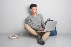 Den unga asiatiska mannen i tillfällig kläder använder en bärbar dator som ler whi Royaltyfri Bild