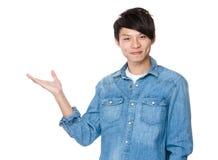 Den unga asiatiska mannen med den öppna handen gömma i handflatan Fotografering för Bildbyråer