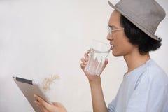 Den unga asiatiska mannen med hatten och exponeringsglas som förvånas på minnestavla- eller bärbar datorstund, dricker ett expone arkivbild