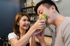 Den unga asiatiska mannen och kvinnan har romantisk tid, medan bli hemma Hemmastatt begrepp för parlivsstil Arkivbilder