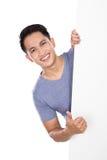 Den unga asiatiska mannen som rymmer en tom banervisning, tummar upp Fotografering för Bildbyråer