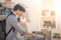 Den unga asiatiska mannen som väljer disketten i musik, shoppar arkivfoto