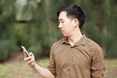 Den unga asiatiska mannen spelar på hans telefon Arkivbild