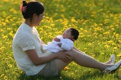 Den unga asiatiska modern med behandla som ett barn flickan på gräs Arkivfoton