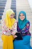 Den unga asiatiska muslimkvinnan i den head halsduken ler tillsammans Arkivbild
