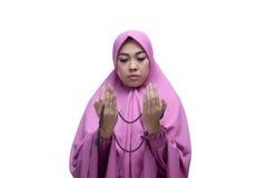 Den unga asiatiska muslimkvinnan med bönpärlor som lyfter handen, ber Arkivbild