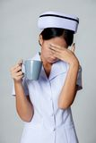 Den unga asiatiska sjuksköterskan får trött arkivfoton