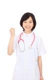 Den unga asiatiska sjuksköterskan rymmer upp nävar Royaltyfria Bilder