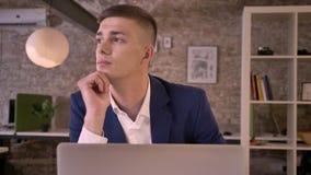 Den unga attraktiva affärsmannen arbetar med bärbara datorn och att hålla ögonen på i fönstret som drömmer begrepp, kommunikation lager videofilmer