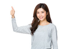 Den unga attraktiva asiatiska kvinnan som ger tummar, up tecknet Royaltyfri Foto