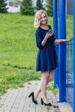 Den unga attraktiva blonda kvinnan i en sommar parkerar Arkivfoto