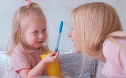 Den unga attraktiva blonda kvinnan kysser hennes lilla charmiga dotter i rosa klänningar med filt-pennor Arkivbild