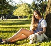 Den unga attraktiva blonda kvinnan som spelar med hennes hund i gräsplan, parkerar Royaltyfria Bilder