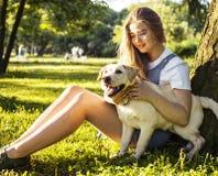 Den unga attraktiva blonda kvinnan som spelar med hennes hund i gräsplan, parkerar Royaltyfri Fotografi