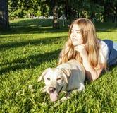 Den unga attraktiva blonda kvinnan som spelar med hennes hund i gräsplan, parkerar Royaltyfri Foto