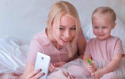 Den unga attraktiva blonda mamman visar något i mobiltelefon till hennes lilla charmiga dotter i rosa klänningar Eller gör Arkivfoto