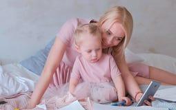 Den unga attraktiva blonda mamman visar något i mobiltelefon till hennes lilla charmiga dotter i rosa klänningar Eller gör Royaltyfri Bild
