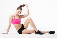 Den unga attraktiva brunbrända spensliga flickan utför sportövningar Royaltyfria Bilder