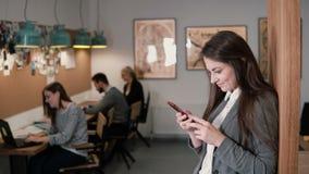 Den unga attraktiva brunettaffärskvinnan använder en pekskärmminnestavla i det moderna startup kontoret royaltyfria foton