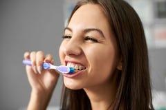 Den unga attraktiva brunetten gör ren hennes tänder med en tandborste och ler och är lycklig härom royaltyfria bilder