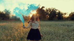 Den unga attraktiva brunettflickan i kjol med en blå rök bombarderar på fältet Flicka som har gyckel som skrattar att tycka om oc stock video