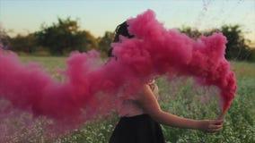 Den unga attraktiva brunettflickan i kjol med en rosa rök bombarderar på fältet Flicka som har gyckel som skrattar att tycka om o stock video