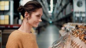 Den unga attraktiva brunettflickan på lagret väljer den ljusa guld- juldekoren royaltyfri fotografi