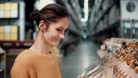 Den unga attraktiva brunettflickan på lagret väljer den ljusa guld- juldekoren royaltyfri foto