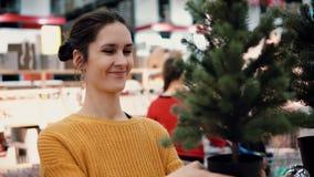 Den unga attraktiva brunettflickan på lagret väljer en konstgjord julgran, julgarnering lager videofilmer