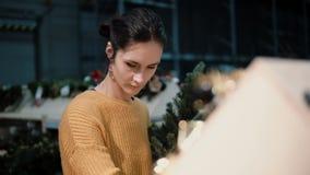 Den unga attraktiva brunettflickan på lagret väljer en konstgjord julgran och leksaker, julgarnering royaltyfria foton