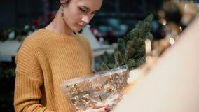 Den unga attraktiva brunettflickan på lagret väljer en konstgjord julgran och leksaker, julgarnering lager videofilmer