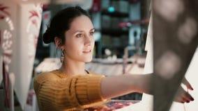 Den unga attraktiva brunettflickan på lagret väljer lampor, juldekor royaltyfri fotografi