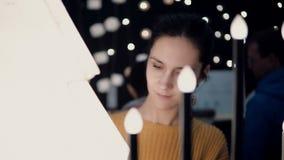 Den unga attraktiva brunettflickan på lagret väljer lampor, juldekor lager videofilmer